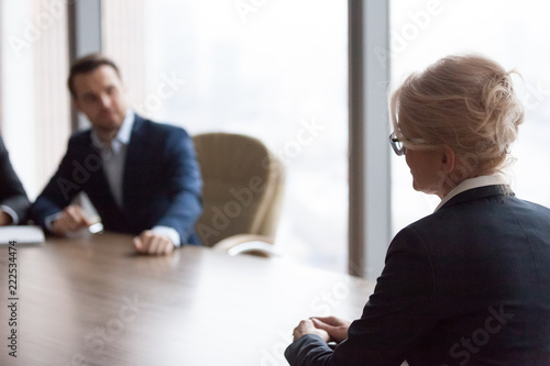 Valokuva  Side view middle ages businesswoman sitting in office at meeting
