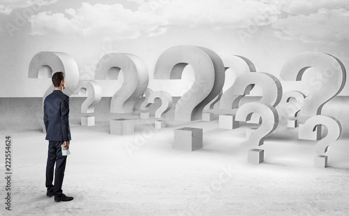 Businessman standing and looking to a bunch of question mark signs