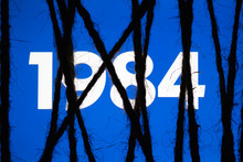 """Smartphone In The Dark, Tightly Wrapped And Tied With Coarse Jute Rope Bondage With Glowing Blue Screen With White Text """"1984"""". Concept Of Censorship On Social Networks. Totalitarianism. Dictatorship"""
