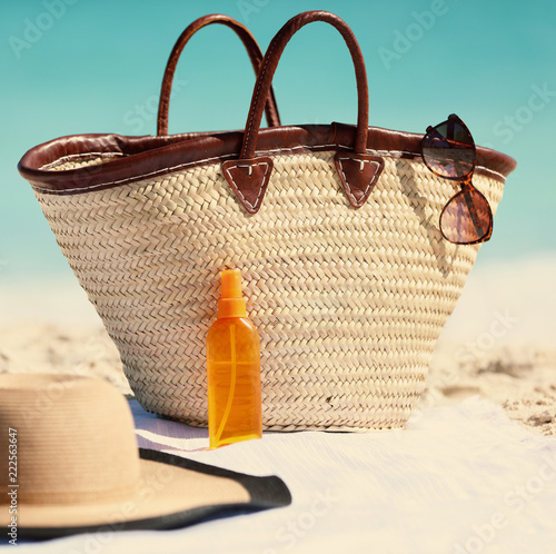 Beach bag and hat, sunglasses and sunscreen lotion