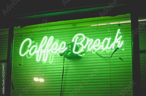 The green neon light sign of the local coffee break in downtown utah.