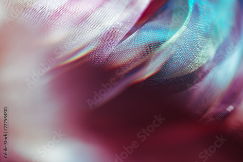 Blurry extreme close up macro of chiffon fabric. Beautiful sensual shapes colorful background. Real optical bokeh effect. Soft, delicate gentle pastel colors. Elegant decorative mesh textile backdrop - 222564810
