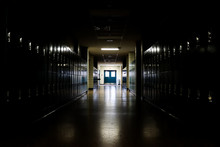 Straight View Of Darkly Lit Hallway With Bright Light At End And Lockers Covering The Walls On Either Side