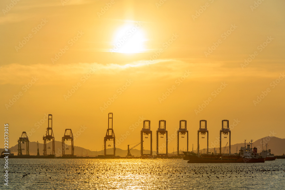 Fototapeta Container Cargo freight ship with working crane bridge in shipyard at the sunset for Logistic Import Export background