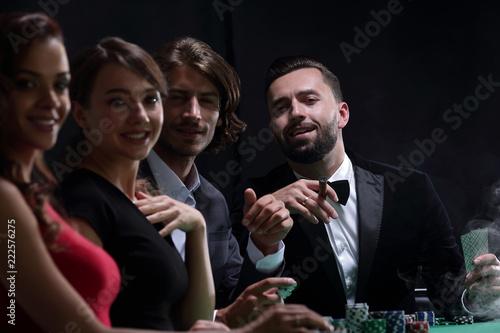 Photographie  Upper class friends gambling in a casino.