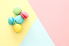 Multicolored Macaroons On Pastel Geometric Background
