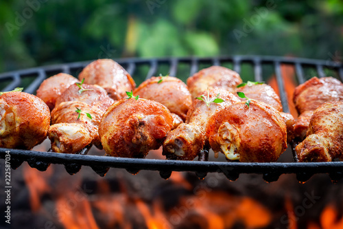 Tasty and spicy chicken leg on grill with flames