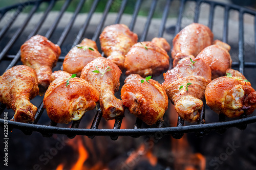 Hot chicken leg on grill with spices and herbs