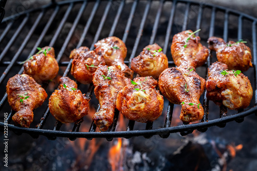 Hot chicken leg on grill with herbs and spices