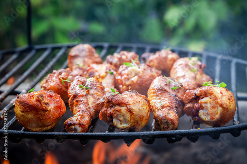 Spicy chicken leg on grill with spices and herbs