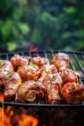 Spicy chicken leg on grill with herbs and spices