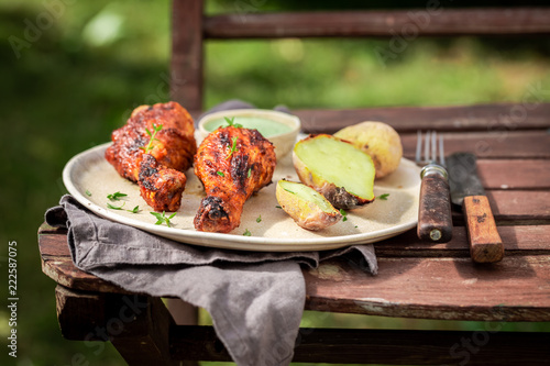 Crispy roasted chicken in hot summer garden