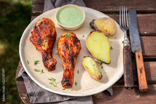 Crispy grilled chicken leg in summer garden