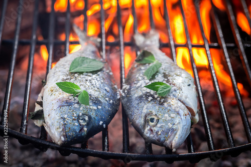 Hot fish on grill with herbs and salt