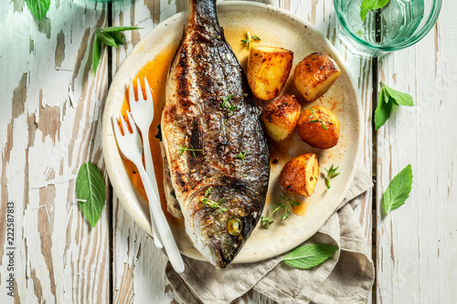 Homemade seabream and potatoes with cherry tomatoes and thyme