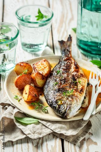 Tasty seabream and potatoes with herbs and tomatoes