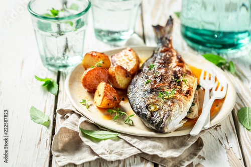 Grilled potatoes and seabream with herbs and tomatoes