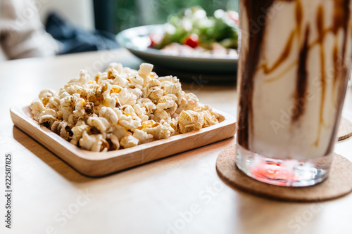 Spoed Fotobehang Voorgerecht Salted popcorn served in square wooden plate on wooden table.