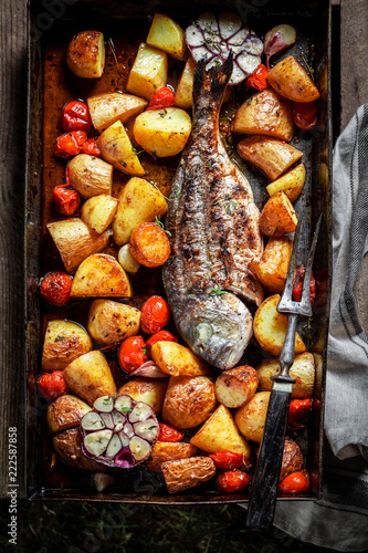 Fresh seabream and potatoes with herbs and tomatoes