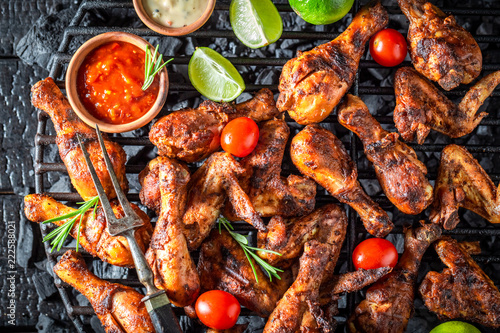 Tasty roasted chicken wings on metal grate