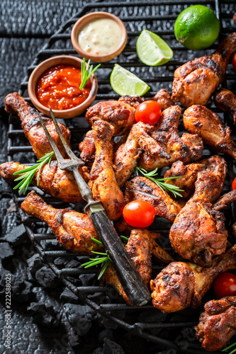 Spicy roasted chicken wings on metal grate