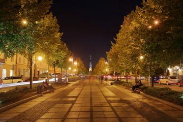 Nocny pejzaż Częstochowy, Polska, główna Aleja Najświętszej Panny Maryi, piękne drzewa po obu stronach, na horyzoncie wieża katedry na Jasnej Górze, długie naświetlanie