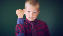 Closeup Portrait Of Angry Caucasian Boy Showing Fist, Demanding Justice, His Rights. Boy Isolated Green Wall Background.