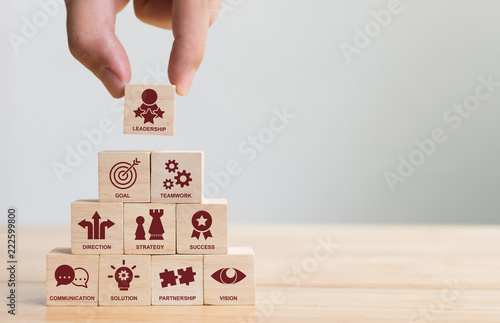 Hand arranging wood block stacking with icon leader business Canvas Print