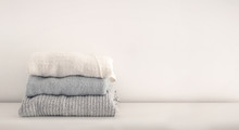 Stack Of Neatly Folded Woolen Knitwear. Minimal Lifestyle, Capsule Wardrobe. Autumn-winter Wardrobe Concept. Light And Airy, Horizontal Copy Space