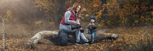family walk in the autumn forest. a caring young mother and her little son sit on an old log of a fallen tree and drink tea from a thermos. dressed in jackets and jeans. panorama with flash light