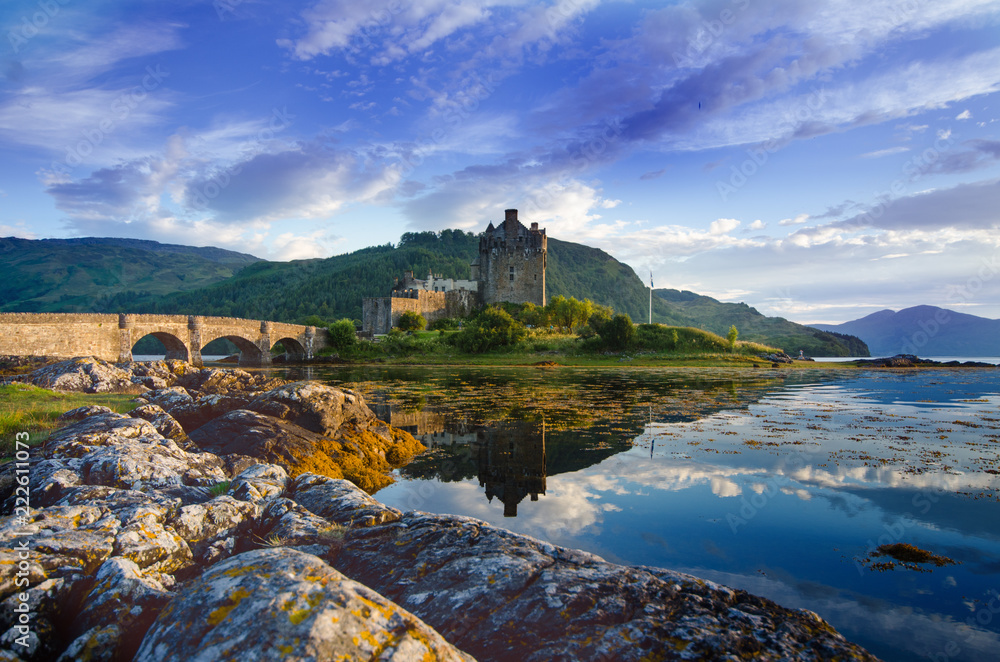 Fototapeta Tourists favourite place in Scotland - Isle of Skye. Very famous castle in Scotland called Eilean Donan castle.  Top of the mountains.Scottish Highlands. Castle with reflection in the lake.