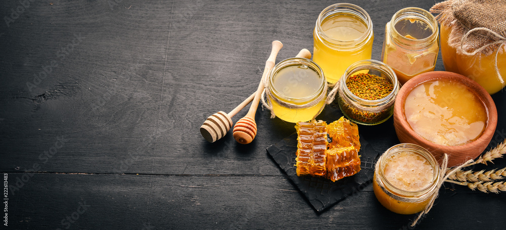 Fototapety, obrazy: A set of honey and bee products. Honey in honeycomb. On a black wooden background. Free space for text. Top view.