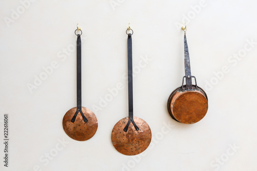 Copper pots and kitchen utinsils hanging on a white painted wall