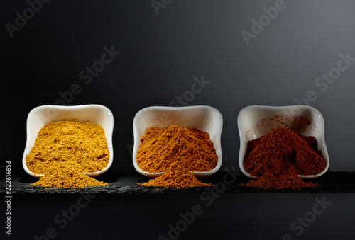 Foto op Aluminium Aromatische Small white ceramic bowls of Indian spices on dark background .