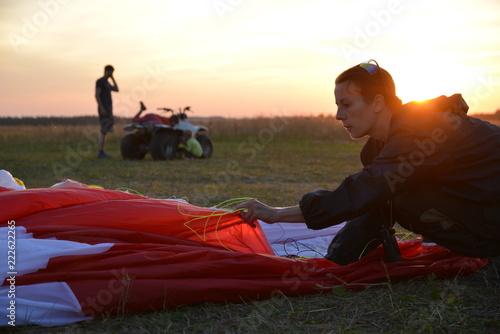 девушка складывает парашют после прыжка