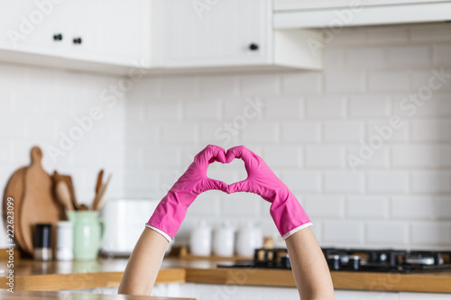 Obraz Heart made of pink protective gloves on white kitchen background.. Woman hands wearing protective gloves. Concept of clean kitchen, successful thumb up yes ok sign - fototapety do salonu