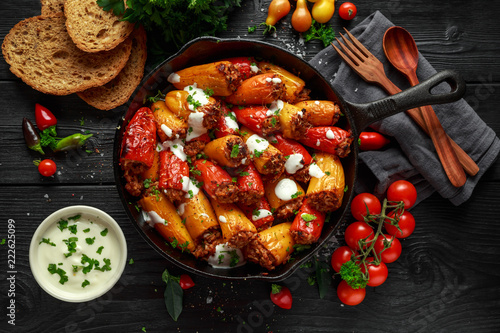 Sausage meat, mince and rice Stuffed sweet mini bell peppers baked in cast iron skillet, pan topped with yogurt and fresh parsley - 222625099