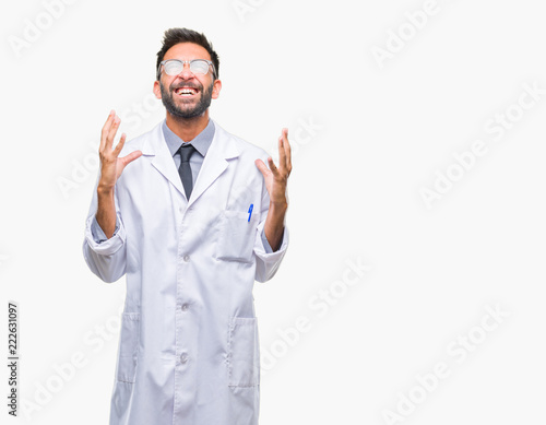 Obraz na płótnie Adult hispanic scientist or doctor man wearing white coat over isolated background crazy and mad shouting and yelling with aggressive expression and arms raised
