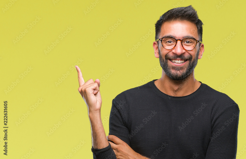Fototapeta Adult hispanic man wearing glasses over isolated background with a big smile on face, pointing with hand and finger to the side looking at the camera.