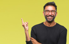 Adult Hispanic Man Wearing Glasses Over Isolated Background With A Big Smile On Face, Pointing With Hand And Finger To The Side Looking At The Camera.