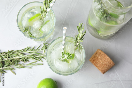 Flat lay composition with lime and rosemary cocktail on gray table