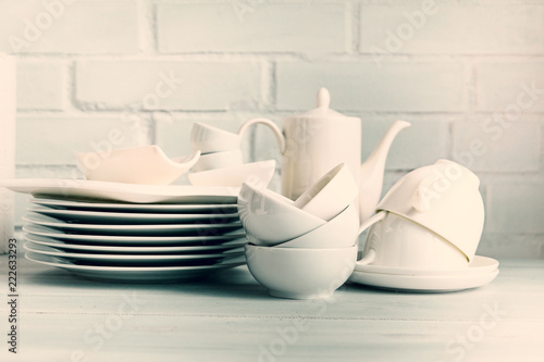 Fotografie, Obraz  White porcelain  dishware stacked on a wooden table against white brick background