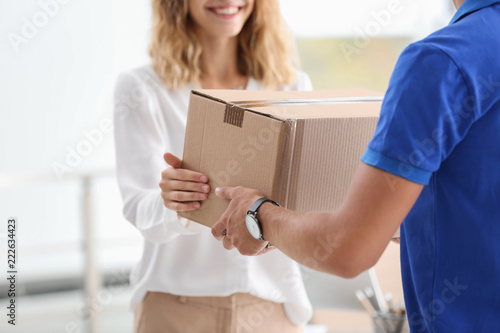 Fényképezés Young woman receiving parcel from courier indoors