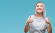 Leinwanddruck Bild - Young blonde woman over isolated background success sign doing positive gesture with hand, thumbs up smiling and happy. Looking at the camera with cheerful expression, winner gesture.