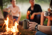 Close Up Cropped Photo. Focus On The Man's Hand Holding Metal Cup. Hikers On The Blurred Background Of The Photo
