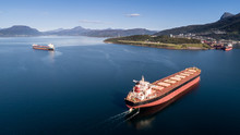 Aerial Shot Of A Cargo Ship On The Open Sea With Other Ship And Mountains In The Background, Narvik, Norway