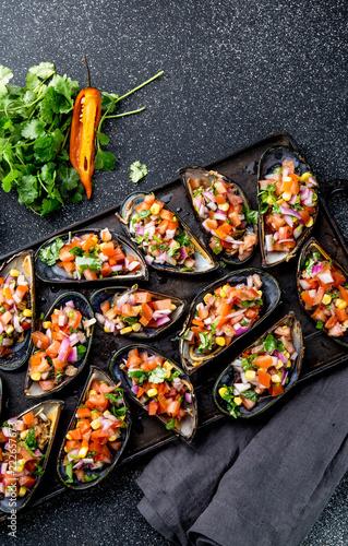 PERUVIAN FOOD. Choros a la chalaca. Big mussels, choros zapatos seasoned with purple onion, tomatoes, corn and lemon. Top view, black background. Traditional peruvian dish