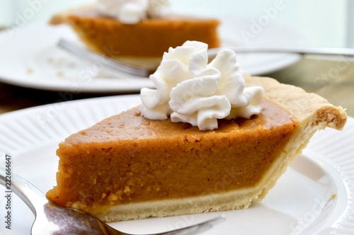 Fényképezés  Slice of pumpkin pie with whipped cream on a white plate with fork