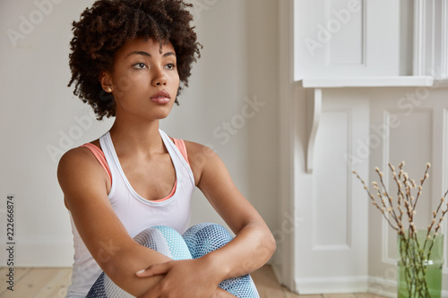 Indoor shot of black thoughtful young woman with Afro haircut, looks pensively into distance, being at home dressed in casual clothes, thinks about starting own business. People and lifestyle concept