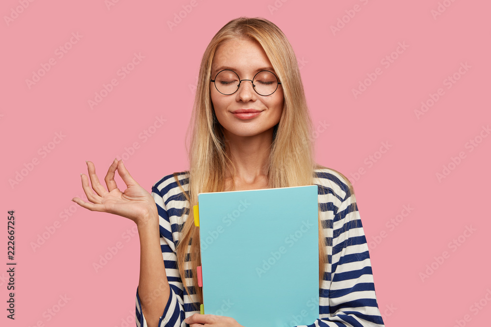 Fototapety, obrazy: Photo of pleasant looking pleased blonde woman makes okay gesture, believes in something good, keeps eyes closed, dressed in casual clothes, isolated over pink background, reads informative book